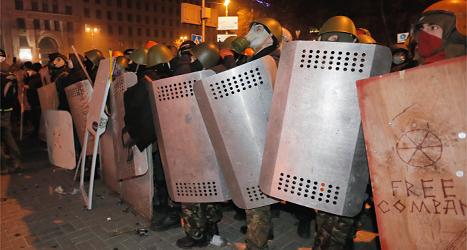 Poliser med sköldar vaktar i staden Kiev i Ukraina.  Foto: Efrem Lukatsky/TT.
