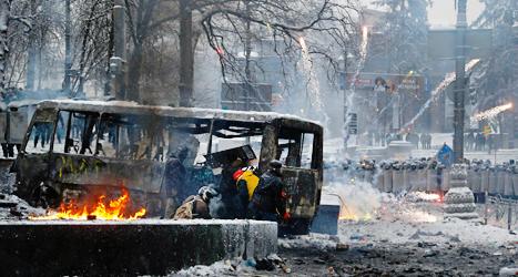 Demonstranter i Kiev gömmer sig bakom en buss som brunnit. Foto: Sergej Grits/TT.