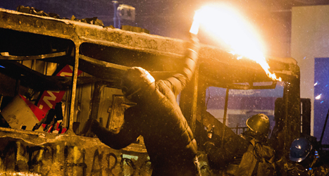 En demonstrant i Kiev kastar en brandbomb mot poliserna. Foto: Evegny Feldman/TT.