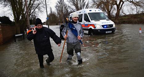 Mäniskor i staden Staines-upon-Thames försöker ta sig fram på en översvämmad gata. Foto: Lefteris Pitarakis /AP /TT