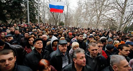 Människor i staden Sevastopol i området Krim protesterar mot förändringarna i Ukraina. De vill att Ukraina hellre ska bli en del av Ryssland. De har med sig en rysk flagga. Foto: Darko Vojinovic /AP /TT