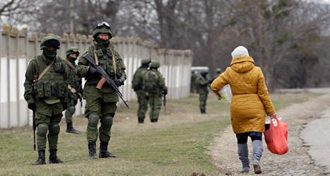 En ukrainsk kvinna går förbi ryska soldater. Foto: Darko Vojinovic/TT.