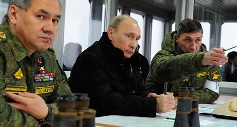 Rysslands ledare Vladimir Putin tillsammans med några ryska militärer. Foto: AP/TT.