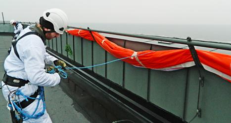 En demonstrant på taket till kärnkraftverket i Oskarshamn. Foto: Greenpeace/TT