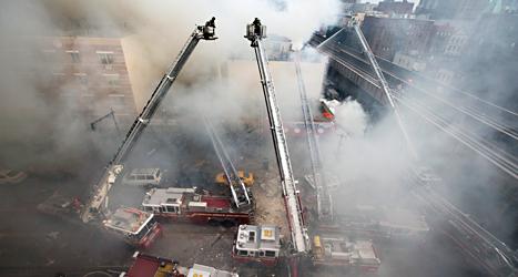 Brandmän försöker släcka elden i husen som exploderat. Foto: John Minchillo/TT.