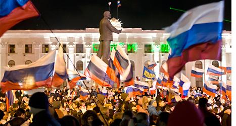 Människor i området Krim firar resultatet i helgens folkomröstning.  De flesta vill att Krim ska bli ryskt. Foto: Vadim Ghirda/TT.