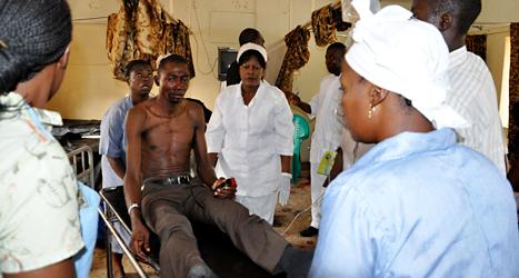 Sjukvårdare tar hand om en man som skadats när bussarna sprängdes i Nigeria. Gbemiga Olamikan/TT.
