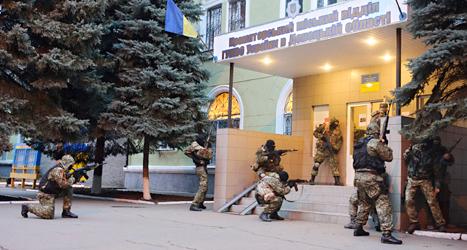 Män med vapen tar sig in på en polisstation i staden Kramatorsk. Bild: TT.