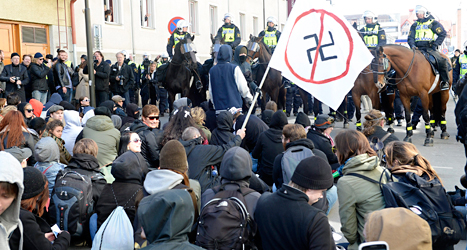 Folk har satt sig på en gata i Jönköping för att stoppa nazisterna. Foto: Mikael Fritzon /TT