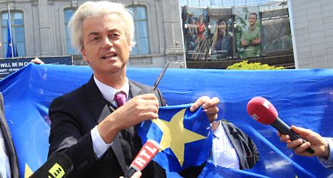 Geert Wilders har klippt sönder flaggan för att visa att han inte gillar EU. Han är ledare för ett högerextremt parti i Nederländerna. Foto: AP/TT