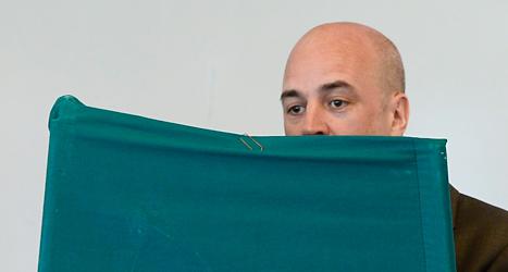 Statsminister Fredrik Reinfeldt står bakom en skärm och gör i ordning sin röst. Han är en av många svenskar som röstat i EU-valet. Foto: TT