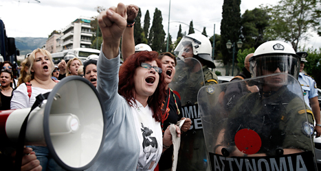 Människor i Grekland protesterar. De har förlorat sina jobb när regeringen sparat pengar. Foto: AP/TT