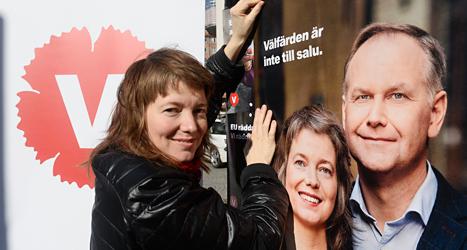Malin Björk sätter upp en affisch med sitt eget ansikte på. Affischen är reklam för Vänsterpartiet. Foto: TT