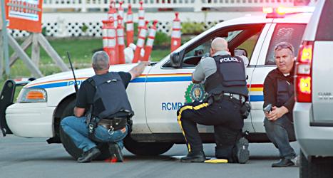 Poliser gömmer sig bakom en bil när de försöker fånga mördaren. Foto: Moncton Times /Ron Ward /TT