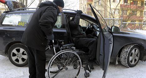 Chauffören hjälper mannen att komma in i taxin. Mannen har färdtjänst. Foto: TT