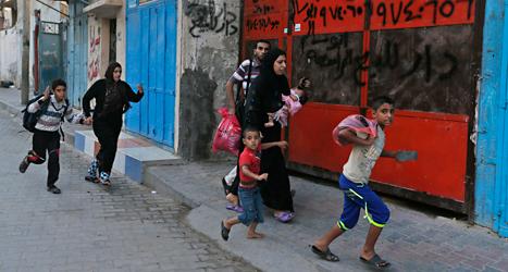 Palestinier springer till ett skyddsrum när Israels bombplan  är på väg mot Gaza. Foto: Lefteris Pitarakis/TT.