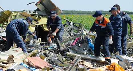 Ukrainska arbetare tar hand om delar från det störtade flygplanet.  Foto: Jevgeniy Maloteka/TT.
