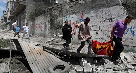 Sjukvårdare tar hand om en palestinier som skadats av Israels bomber.
