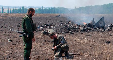 Några rebeller tittar på delar från ett nerskjutet ukrainskt stridsflygplan. Foto: AP/TT.