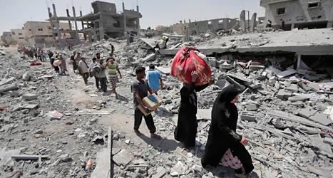 Människor i Gaza lämnar sina förstörda hus på fredagen. Foto: Lefteris Pitarakis/AP/TT