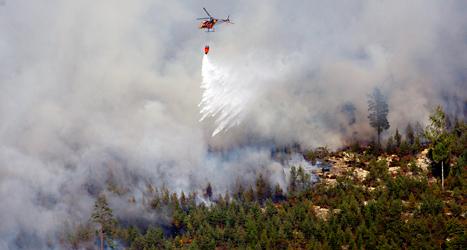 Ett flera kilometer stort område brinner utanför Sala. En helikopter släpper vatten på branden. Foto: Jocke Berglund /TT