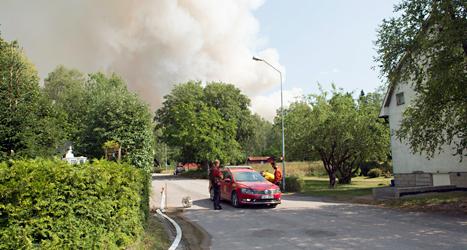 Röken från branden syns från byn Gammelby. Människorna får inte stanna kvar där längre. Foto: Fredrik Sandberg /TT