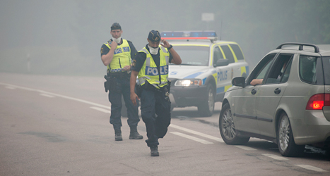 Poliserna stoppar människor från att åka in i området där det brinner. Foto: Fredrik Sandberg, TT