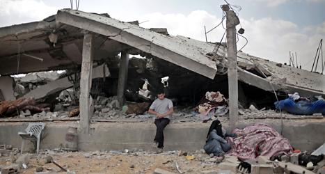 En man sitter utanför ett förstört hus i staden Shawkat i Gaza. Området Gaza är helt förstört efter Israels attacker. Foto: Khalil Hamra, AP/TT