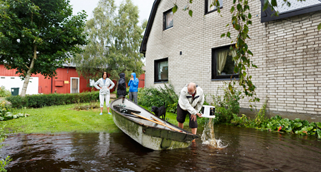 Mikael Jönsson, Camilla Broberg och deras barn får använda båt för att komma ifrån sitt hus. Foto: Anders Andersson /TT