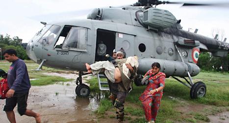 Människor i Indien räddas undan översvämningarna. Foto: AP/TT.