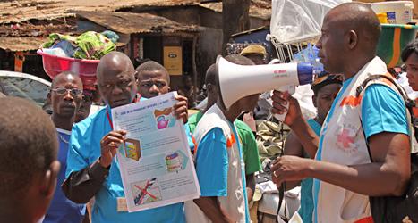 Sjukvårdare talar om för människor hur de ska skydda sig mot ebola-viruset. Foto: Youssouf Bah/TT.