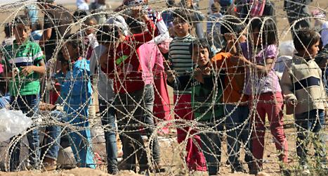 Flyktingar från Syrien väntar på att få komma in i grannlandet Turkiet. Foto: Burhan Ozbilici/TT.