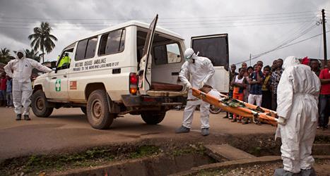 Sjukvårdare i skyddsdräkter tar hand om en man som kan vara sjuk i ebola. Foto: Tanay Bindra /TT