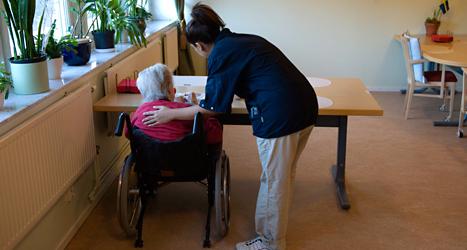 En sköterska tar hand om en gammal människa på ett hem. Foto: TT