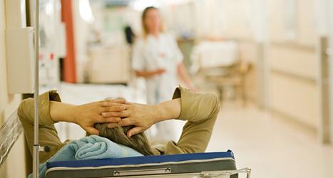 En sjuk person ligger i en säng på sjukhuset. Foto: TT