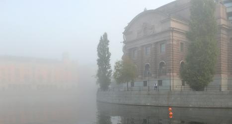 Riksdagshuset i dimma. Här kommer politikerna att rösta om flera viktiga frågor i höst. Foto: TT