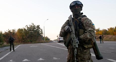 En soldat i Ukraina vaktar en väg. Det är krig mellan olika grupper i landet. Foto: AP/TT