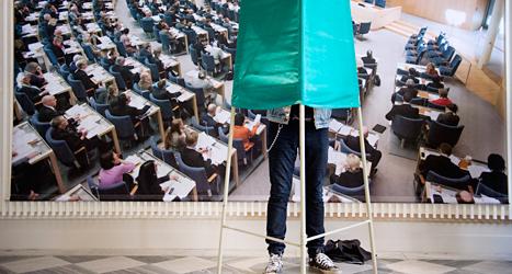 En person röstar framför en bild på politikerna i riksdagen. Foto: TT