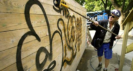 En man tvättar bort klotter på en vägg vid en skola i Stockholm. Foto: Gunnar Lundmark/TT.