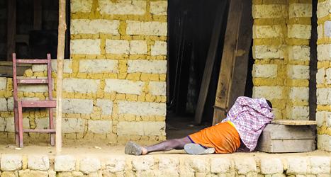 En ebolasjuk man ligger på gatan utanför ett hus i staden Freetown  i Sierra Leone. Foto: Michael Duff/TT.