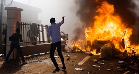 En bil brinner utanför riksdagshuset i landet Burkina Faso: Foto: Theo Renault/TT.