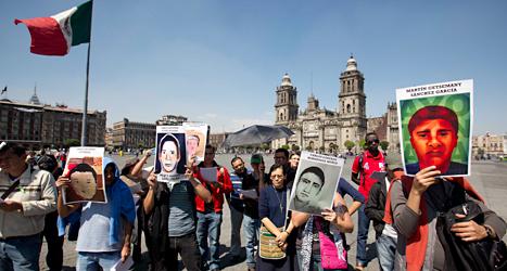 Människor demonstrerar i Mexiko. De håller upp bilder på sina mördade släktingar. Foto: Eduardo Verdugo/TT.