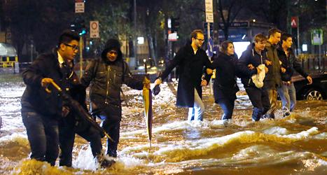 Människor i Italien håller varandra i händerna när de går över en översvämmad väg. Foto: Luca Bruno/TT