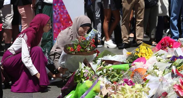 Människor lägger ner blommor utanför kaféet där tre människor dödades.