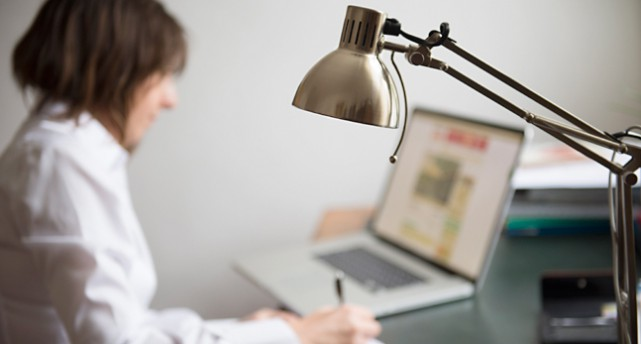 En kvinna jobbar vid sin dator