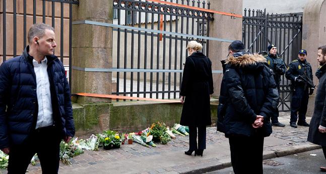 Danmarks statsminister Helle Thorning-Scmhmidt står med böjt huvud framför synagogan där terroristen dödade en man. Det ligger blommor på marken utanför synagogan. Vakter och poliser finns på platsen.