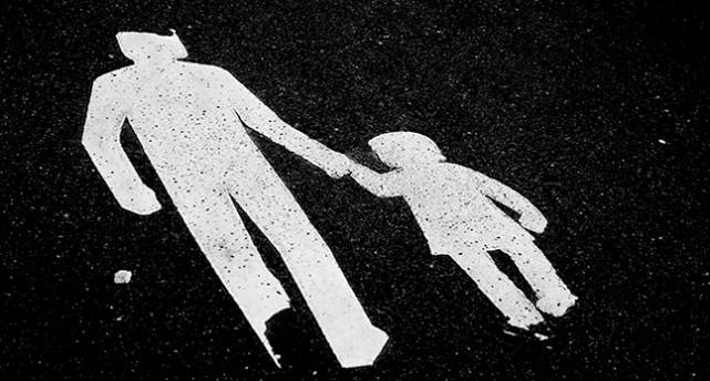 Bilden på gatan visar en vuxen som håller ett barn i handen.
