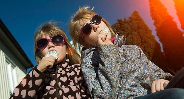 Två kvinnor i Stockholm njuter av vårsolen.