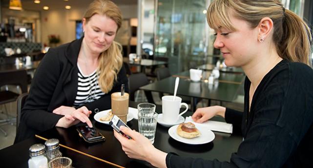 De fikar och använder mobiltelefonen