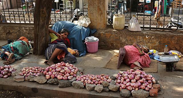 Försäljare som säljer lök på trottoaren